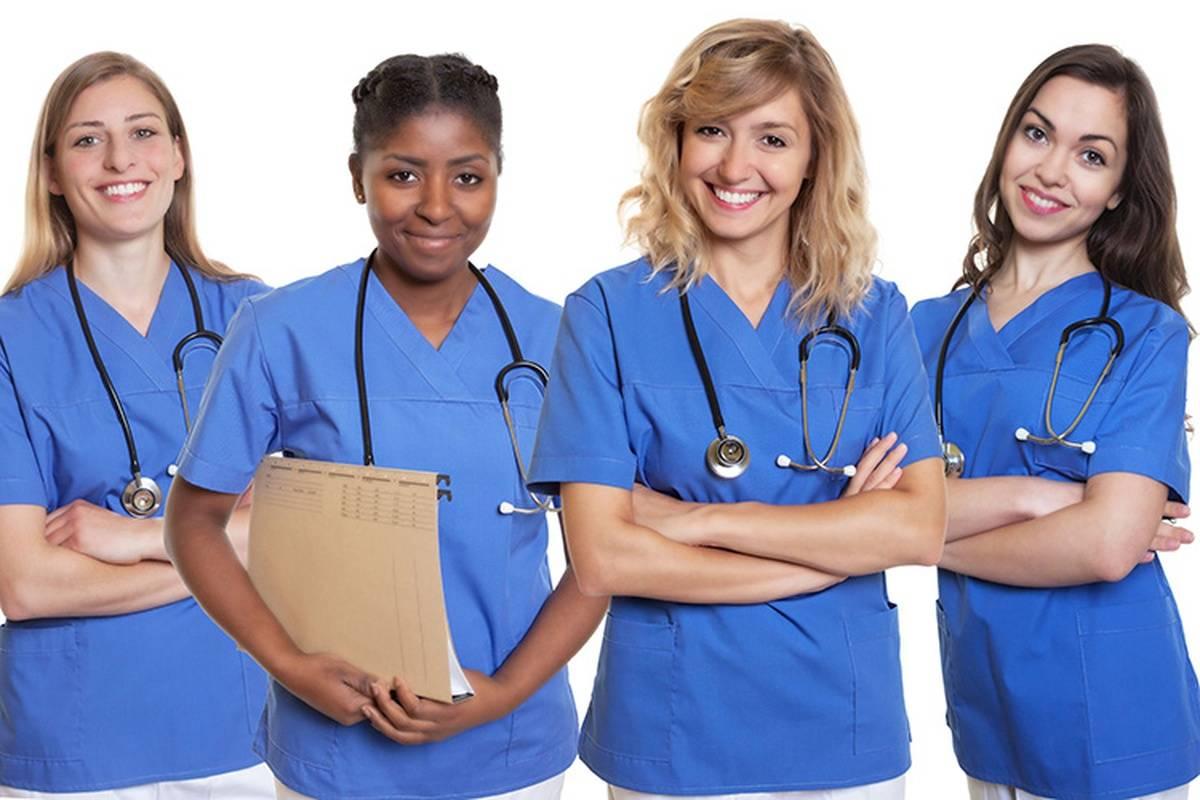 Four nurses in blue scrubs posing