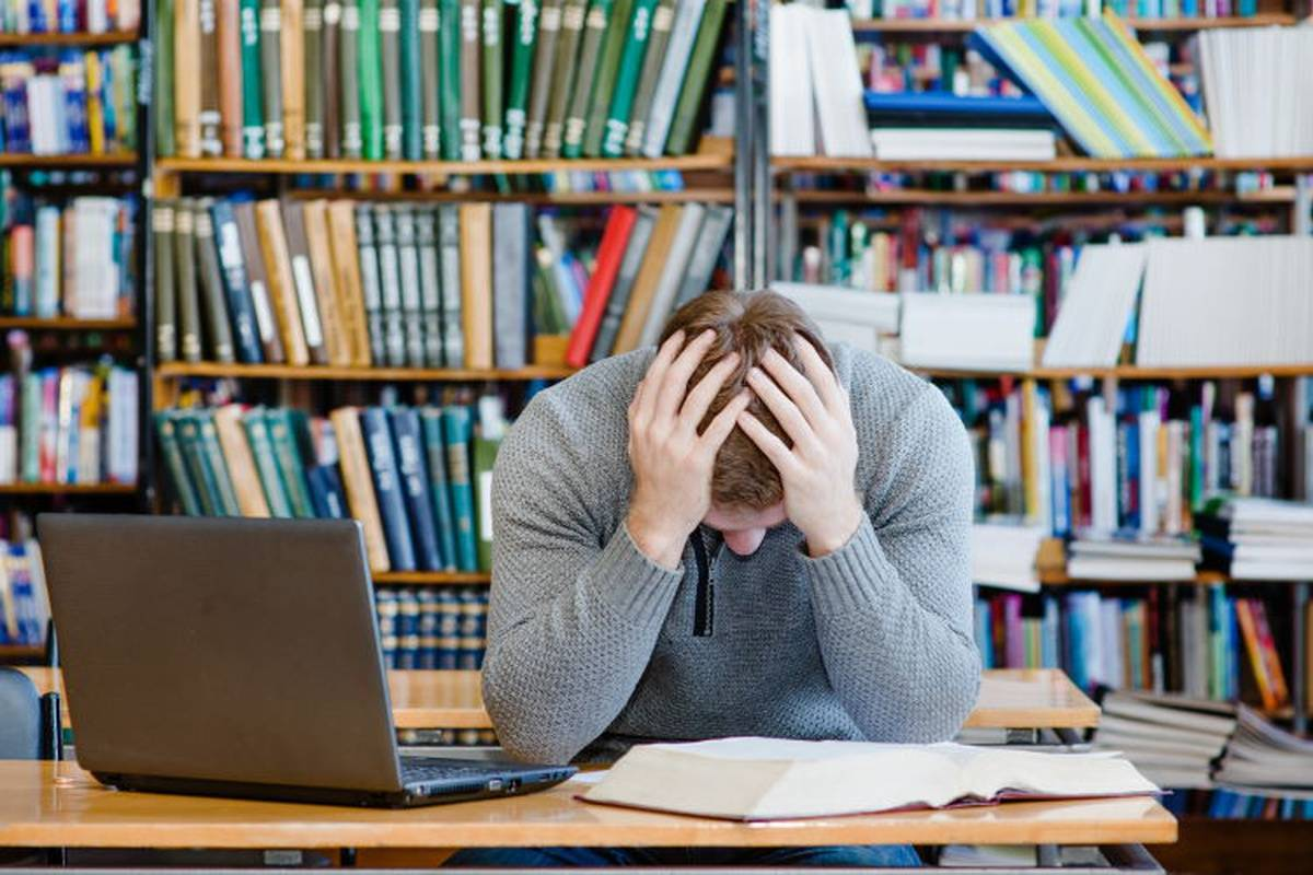 Man studying in library holding head in his hands