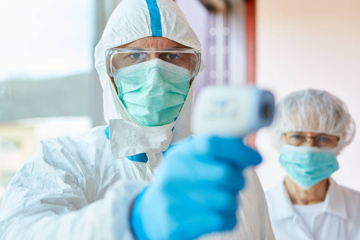 Two healthcare workers wearing PPE and taking patient's temperature