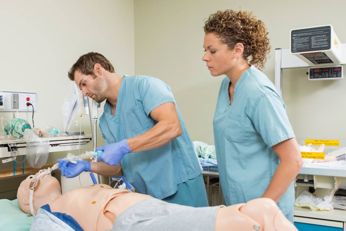 One nurse teaching another CPR on a practice dummy