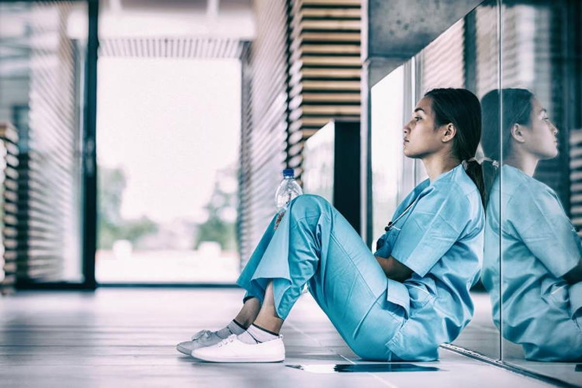 Distressed nurse sitting in empty hospital hallway