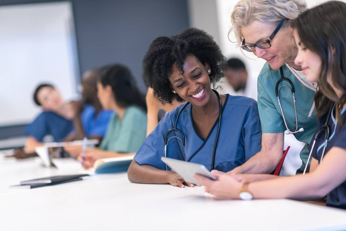 Senior female lecturer assists medical students during class