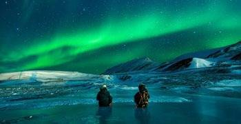 Two people sitting on frozen lake enjoying aurora borealis in Alaska