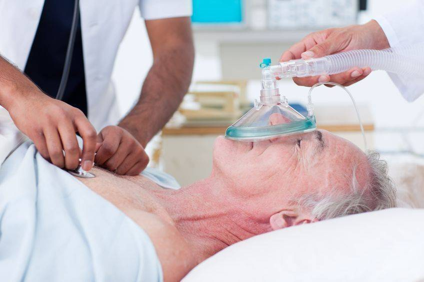 Elderly patient with oxygen and doctor checking heartbeat