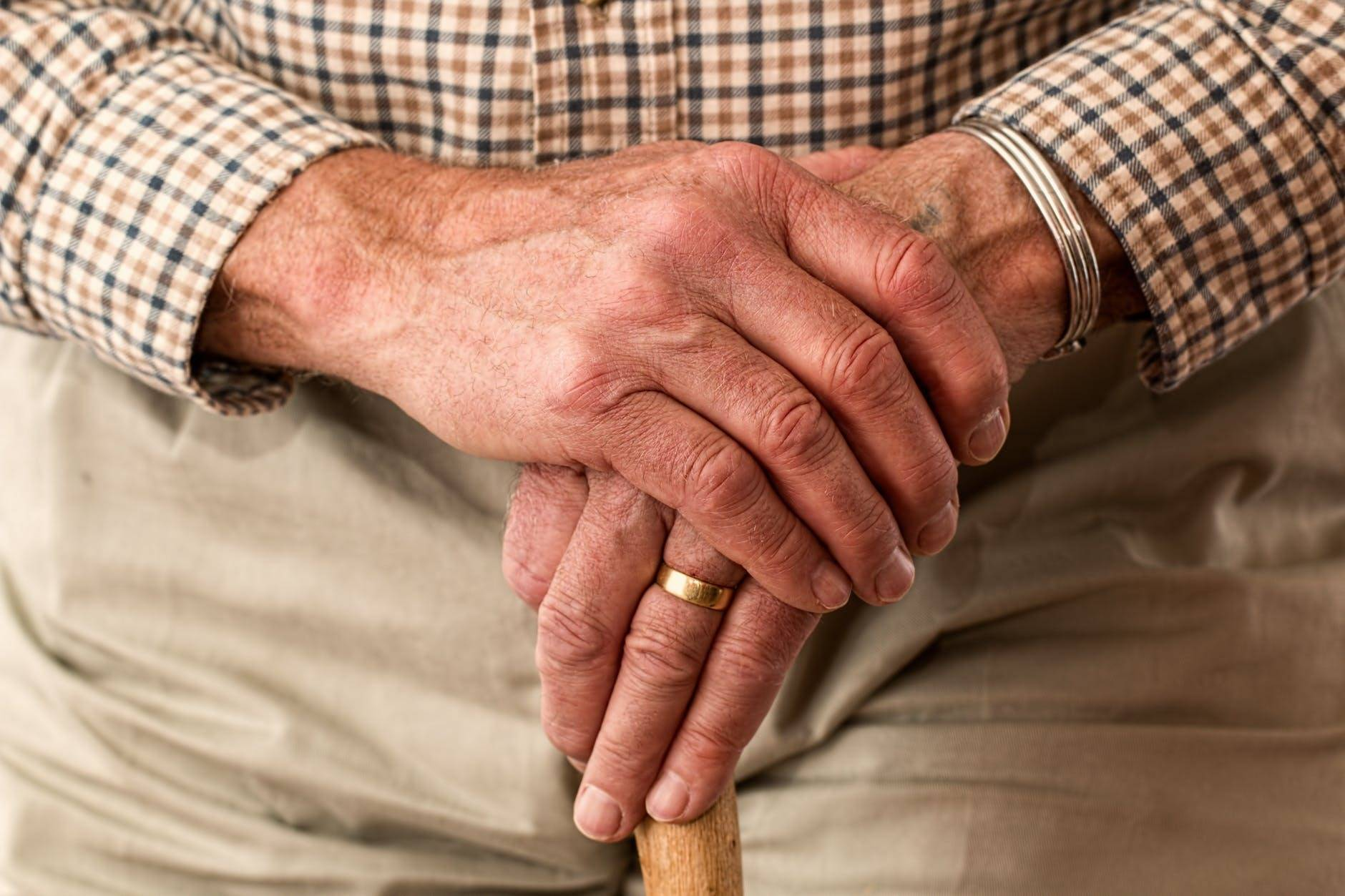 Elderly man with crossed hands, cane, and wedding band