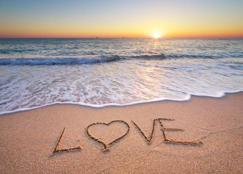 Beach with waves rolling in and love etched into the sand