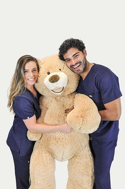 Two nurses in scrubs holding giant teddy bear