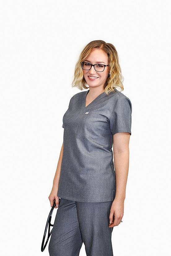 Female nurse holding stethoscope modeling gray scrubs