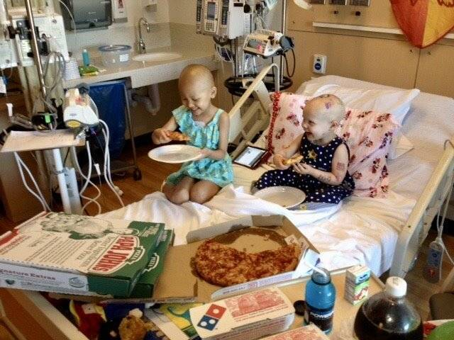 Two child patients in hospital bed eating pizza
