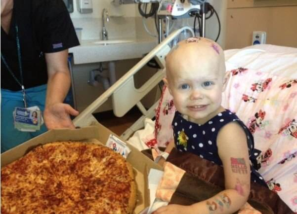 Child cancer patient smiling next to pizza