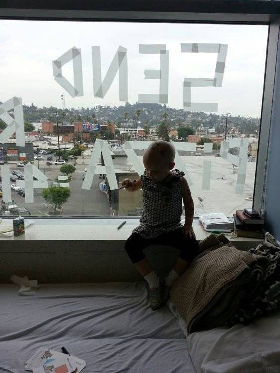 Child patient looking out high up hospital window