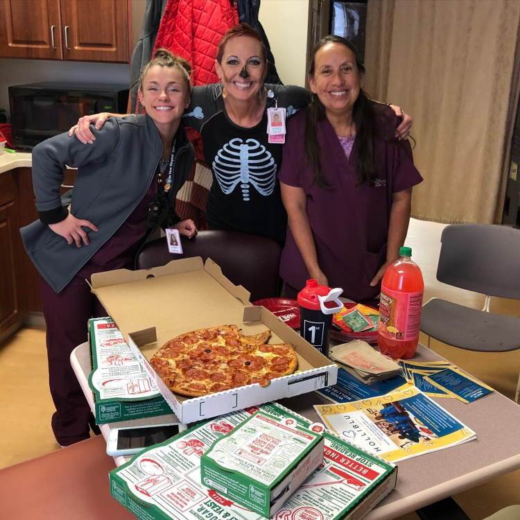 Healthcare workers on halloween next to pizza