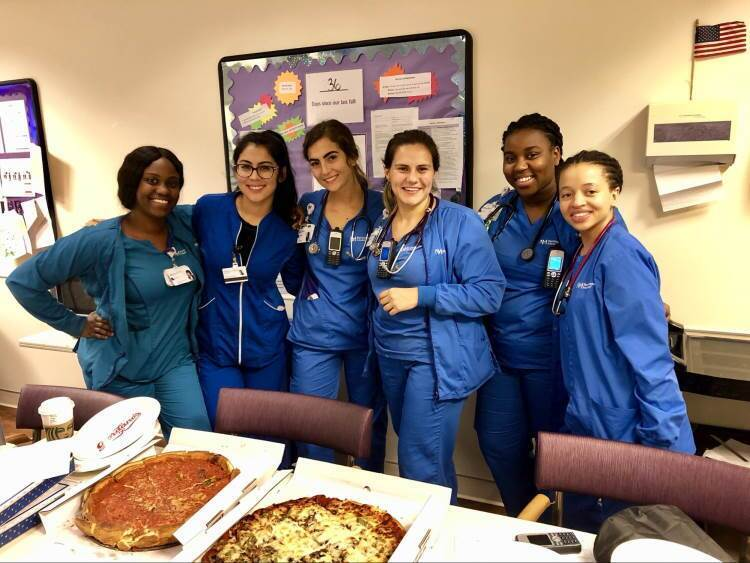 Group of nurses in break room with pizzas