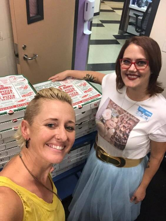 Two women with stacks of pizza boxes