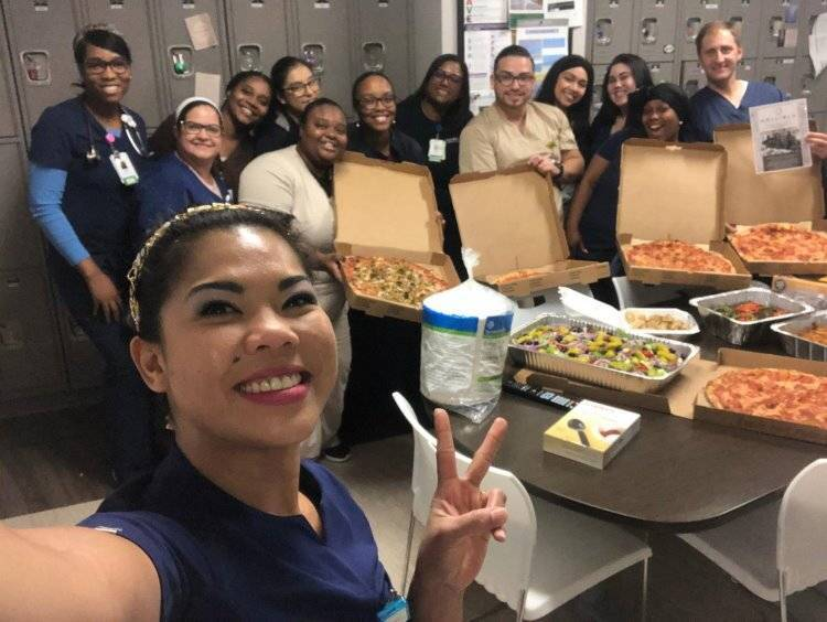 Nurse holding peace sign with group of healthcare workers and pizza