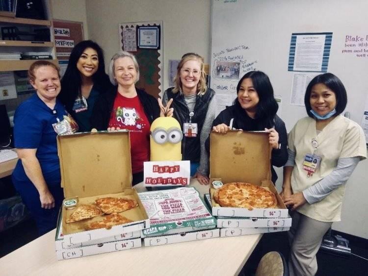 Nurses smiling next to table with pizzas