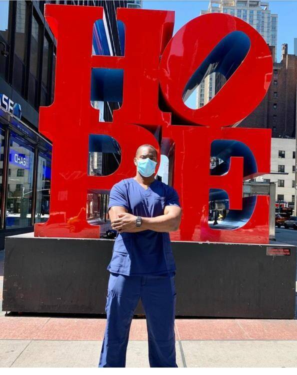 Nurse with face mask in front of nyc hope sign