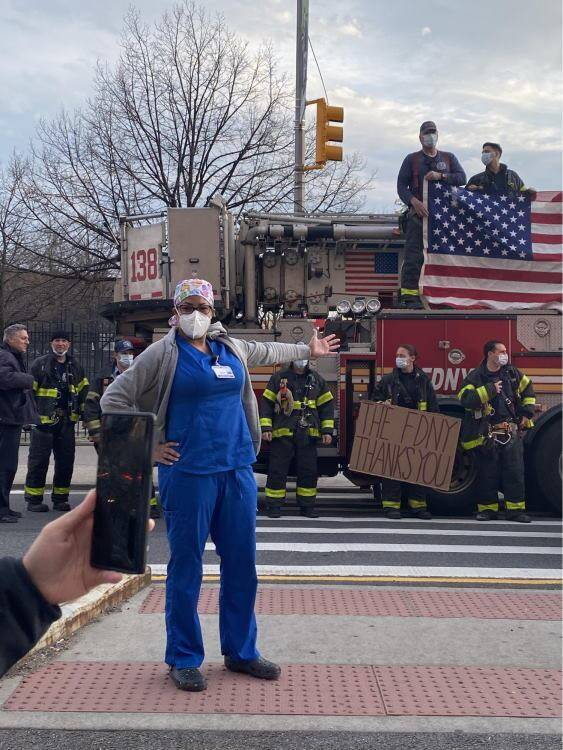 Nurse outdoors in new york city with nyfd thank you signs