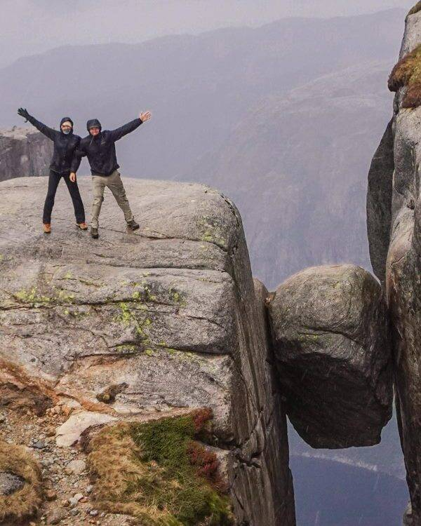 Two people standing on rock on mountain