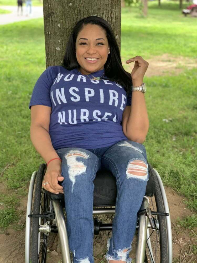Nurse in wheelchair outdoors in front of tree